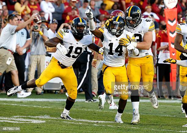 Defensive back Desmond King of the Iowa Hawkeyes celebrates with teammates Miles Taylor and Josey Jewell after intercepting a pass intended for wide...