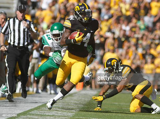 Defensive back Desmond King of the Iowa Hawkeyes is knocked out of bounds in the first half by running back Andrew Tucker of the North Texas Mean...