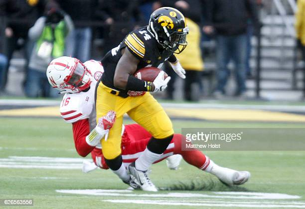 Defensive back Desmond King of the Iowa Hawkeyes is tackled by safety Antonio Reed of the Nebraska Huskers during the first quarter on November 25...