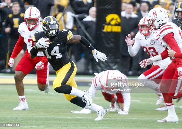 Defensive back Desmond King of the Iowa Hawkeyes runs in front of safety Antonio Reed of the Nebraska Huskers during the first quarter on November 25...