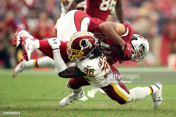Defensive back DJ Swearinger of the Washington Redskins tackles wide receiver Larry Fitzgerald of the Arizona Cardinals during the fourth quarter at...