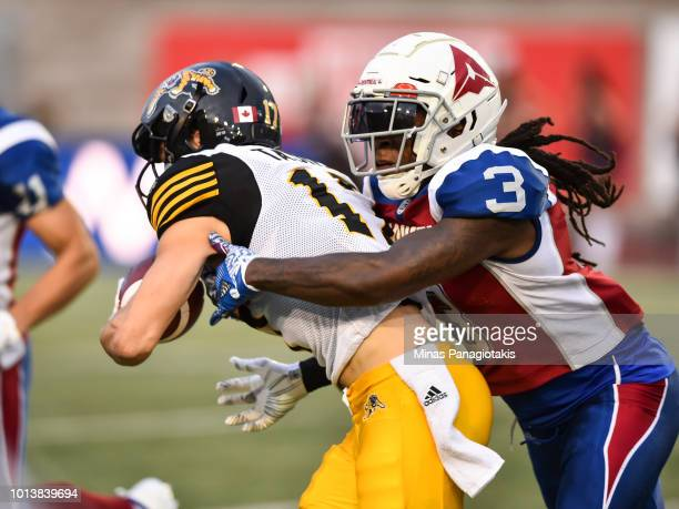 Defensive back Dominique Ellis of the Montreal Alouettes grabs a hold of wide receiver Luke Tasker of the Hamilton TigerCats during the CFL game at...