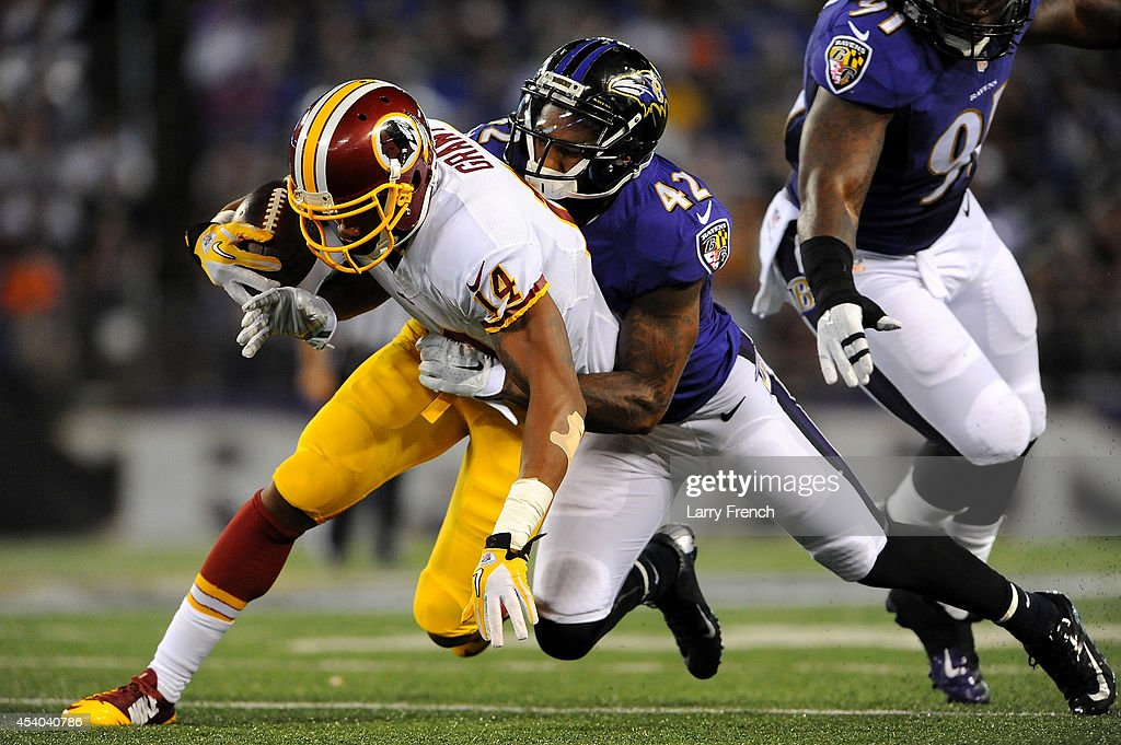 Defensive back Dominique Franks #42 of the Baltimore Ravens tackles wide receiver Ryan Grant #14 of the Washington Redskins during a preseason game at M&T Bank Stadium on August 23, 2014 in Baltimore, Maryland.