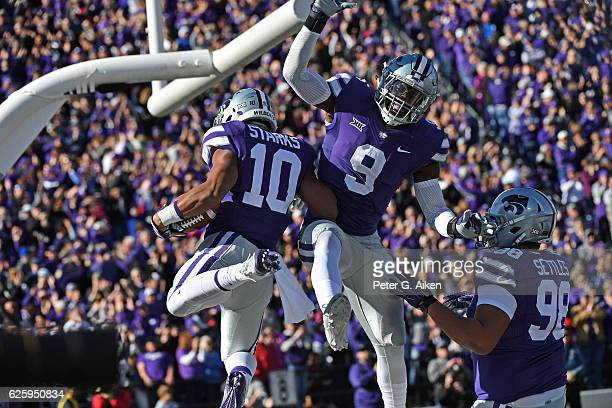 Defensive back Donnie Starks of the Kansas State Wildcats celebrates with teammate Elijah Lee after returning an intercepting for a touchdown against...