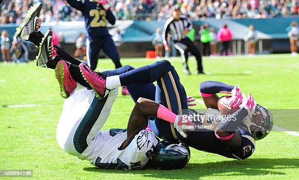 Defensive back EJ Gaines of the St Louis Rams intercepts a pass and is tackled by wide receiver Jeremy Maclin of the Philadelphia Eagles in the...