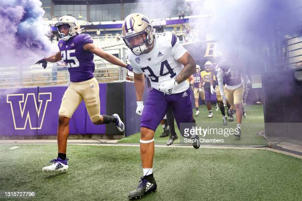 Defensive back Elijah Jackson and running back Capassio Cherry of the Washington Huskies take the field before the spring game at Husky Stadium on...