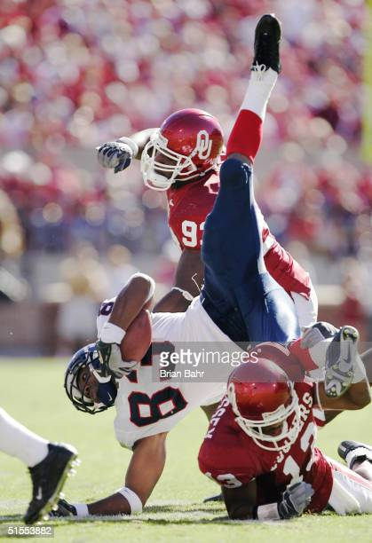 Defensive back Eric Bassey of the Oklahoma Sooners trips up wide receiver Mark Simmons of the Kansas Jayhawks for a loss of a yard in the fourth...