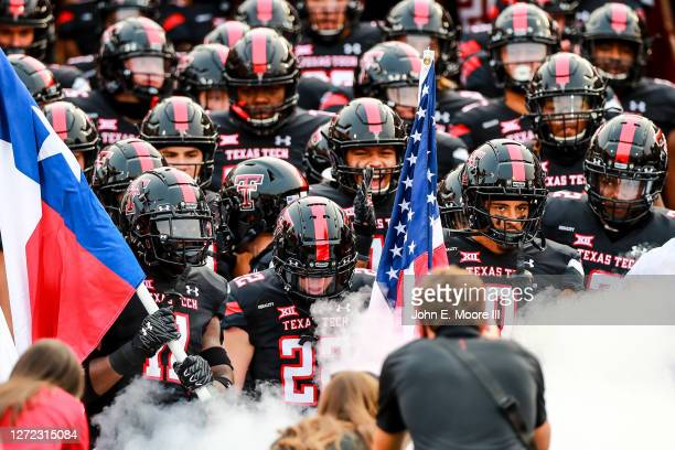 Defensive back Eric Monroe, receiver Sterling Galban, and receiver Seth Collins of the Texas Tech Red Raiders lead their teammates onto the field...