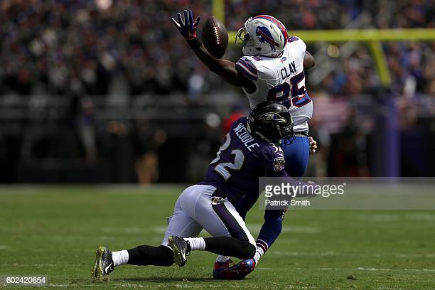 Defensive back Eric Weddle of the Baltimore Ravens tackles tight end Charles Clay of the Buffalo Bills while attempting to catch the ball in the...