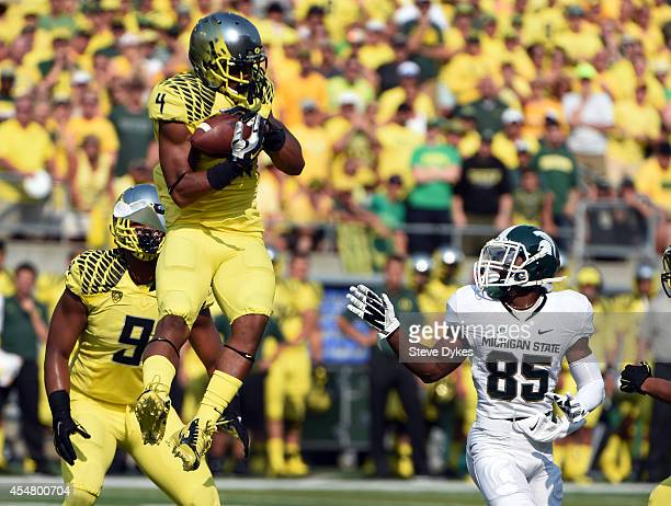 Defensive back Erick Dargan of the Oregon Ducks intercepts a pass intended for wide receiver Macgarrett Kings Jr #85 of the Michigan State Spartans...
