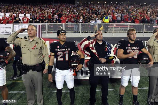 Defensive back Feena Phakasoum and place kicker Evan Pantels of the UNLV Rebels stand with first responders as the American national anthem is...