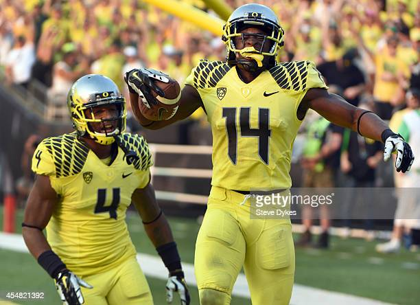 Defensive back Ifo EkpreOlomu of the Oregon Ducks celebrates with defensive back Erick Dargan of the Oregon Ducks after intercepting a pass during...