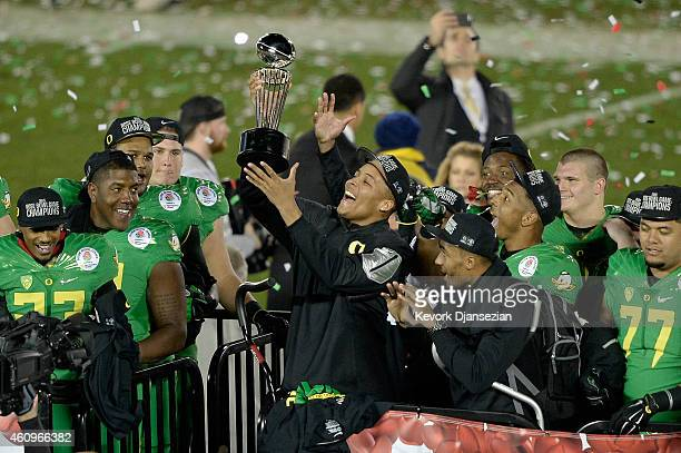 Defensive back Ifo EkpreOlomu of the Oregon Ducks celebrates with the Leishman Trophy after defeating the Florida State Seminoles 5920 in the College...