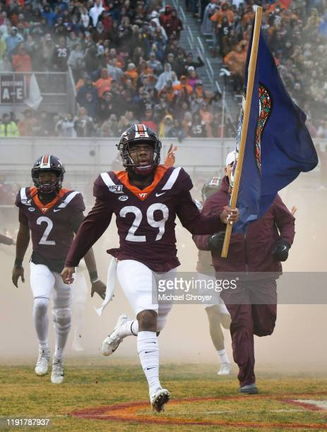 Defensive back Ishmiel Seisay of the Virginia Tech Hokies carries the Virginia flag onto the field prior to the game against the Pittsburgh Panthers...