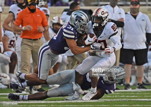 Defensive back Jahron McPherson and linebacker Elijah Sullivan of the Kansas State Wildcats tackle wide receiver Brennan Presley of the Oklahoma...