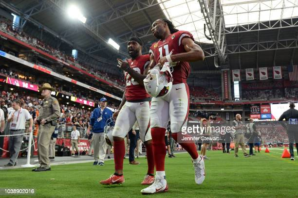 Defensive back Jamar Taylor and wide receiver Larry Fitzgerald of the Arizona Cardinals walk off the field after the NFL game against the Chicago...