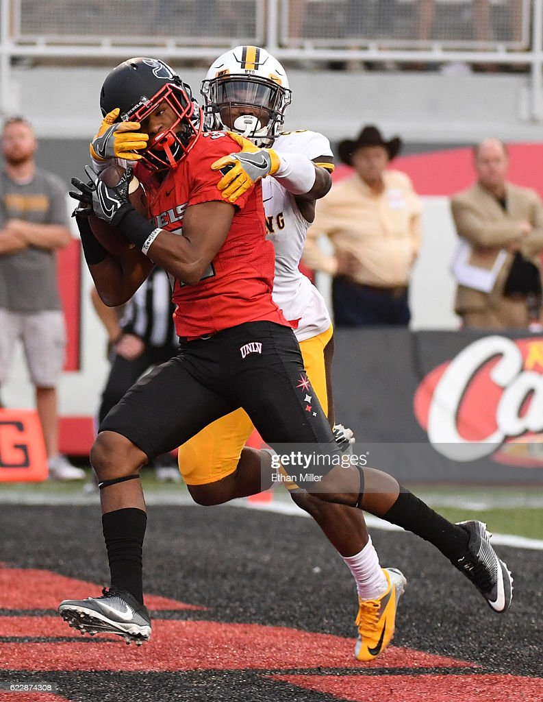 Defensive back Jericho Flowers #32 of the UNLV Rebels catches a touchdown pass in the first overtime against cornerback Rico Gafford #5 of the Wyoming Cowboys during their game at Sam Boyd Stadium on November 12, 2016 in Las Vegas, Nevada. UNLV won 69-66 in triple overtime.