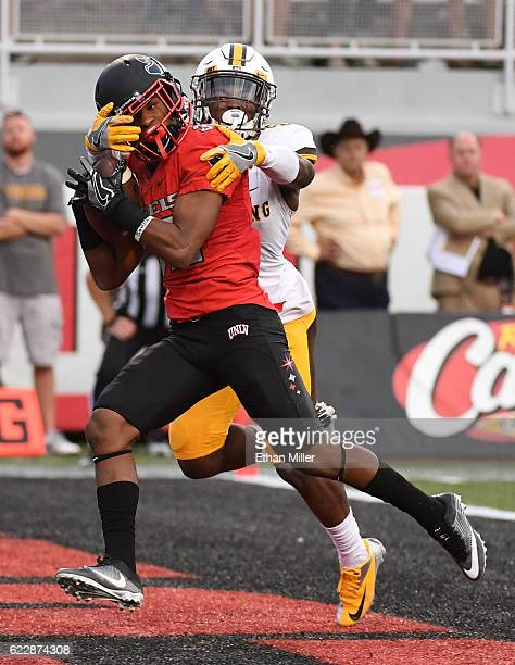 Defensive back Jericho Flowers of the UNLV Rebels catches a touchdown pass in the first overtime against cornerback Rico Gafford of the Wyoming...