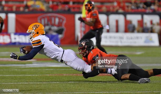 Defensive back Jericho Flowers of the UNLV Rebels tackles wide receiver Terry Juniel of the UTEP Miners during their game at Sam Boyd Stadium on...