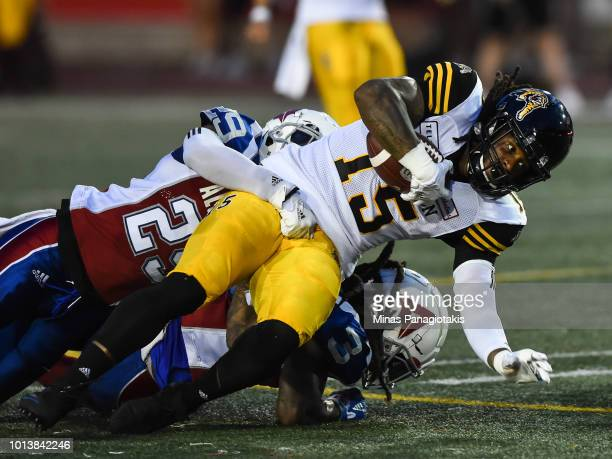 Defensive back Jermaine Robinson of the Montreal Alouettes tackles defensive back Alex Green of the Hamilton TigerCats during the CFL game at...