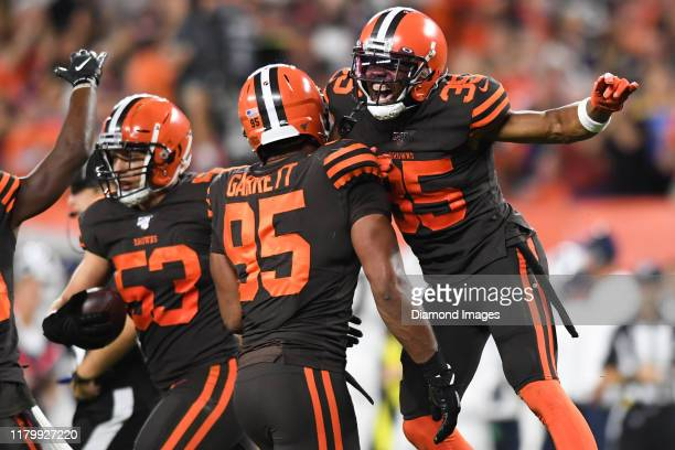 Defensive back Jermaine Whitehead and defensive end Myles Garrett of the Cleveland Browns celebrate a fumble recover by middle linebacker Joe...