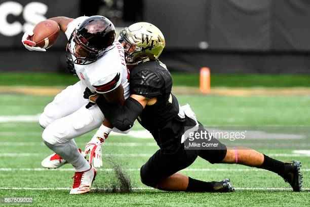 Defensive back Jessie Bates III of the Wake Forest Demon Deacons tackles wide receiver Dez Fitzpatrick of the Louisville Cardinals during the...