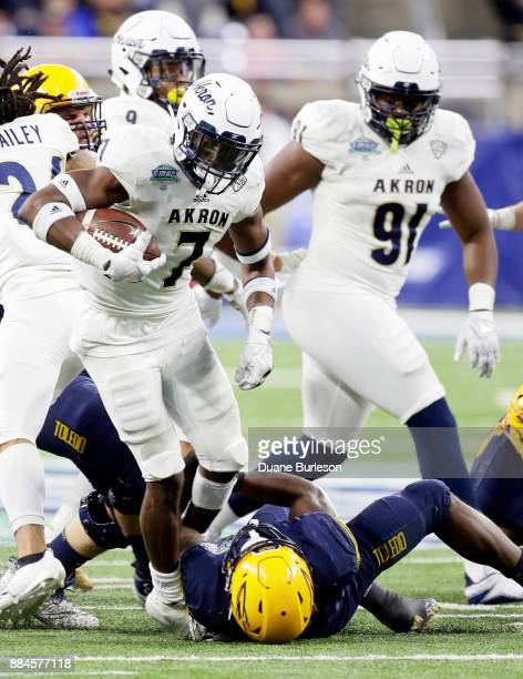 Defensive back Jordan George of the Akron Zips is tackled by running back Terry Swanson of the Toledo Rockets while returning an interception during...