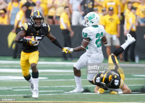 Defensive back Josh Jackson of the Iowa Hawkeyes returns a kick during the fourth quarter in front of linebacker EJ Ejiya of the North Texas Mean...