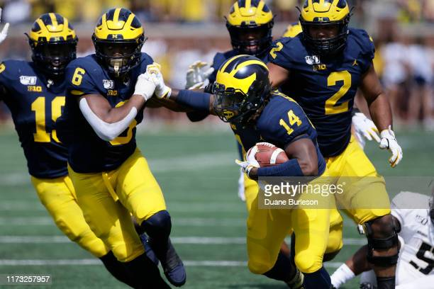 Defensive back Josh Metellus of the Michigan Wolverines returns a Army Black Knights fumble with linebacker Josh Uche and defensive lineman Carlo...