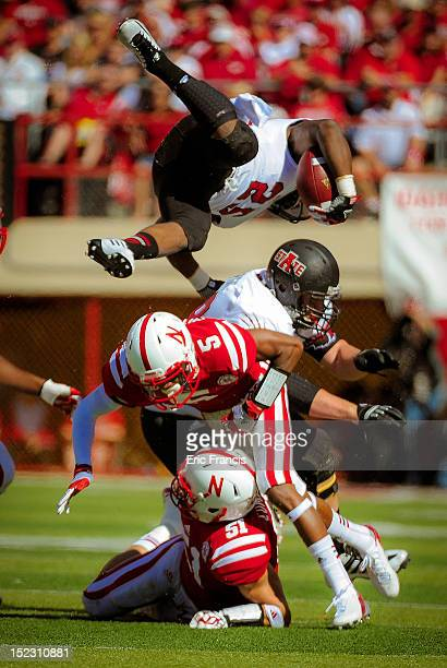 Defensive back Josh Mitchell and linebacker Will Compton of the Nebraska Cornhuskers upend running back David Oku of the Arkansas State Red Wolves...
