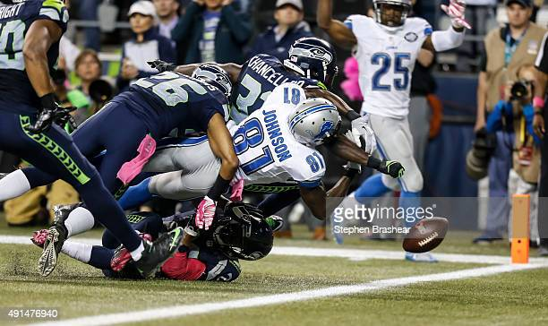 Defensive back Kam Chancellor of the Seattle Seahawks knocks the ball out of the hands of wide receiver Calvin Johnson of the Detroit Lions near the...