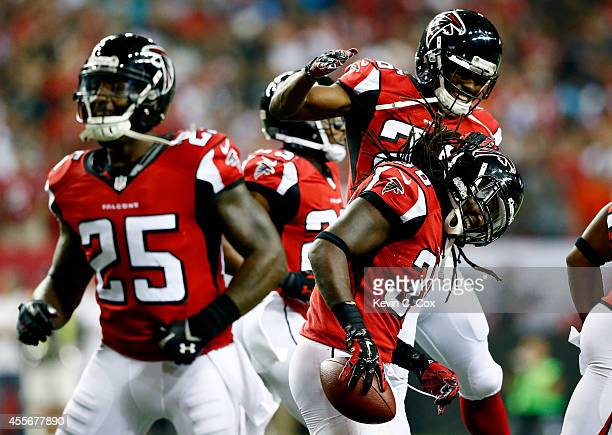 Defensive back Kemal Ishmael celebrates an interception and touchdown with cornerback Josh Wilson of the Atlanta Falcons against the Tampa Bay...