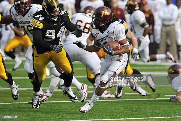 Defensive back Kevin Whaley of the Minnesota Golden Gophers runs away from Defensive lineman Adrian Clayborn of the Iowa Hawkeyes in the first half...