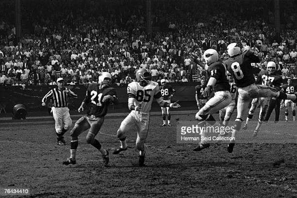 Defensive back Larry Wilson of the St Louis Cardinals intercepts a pass intended for flanker Clifton McNeil of the Cleveland Browns during a game on...