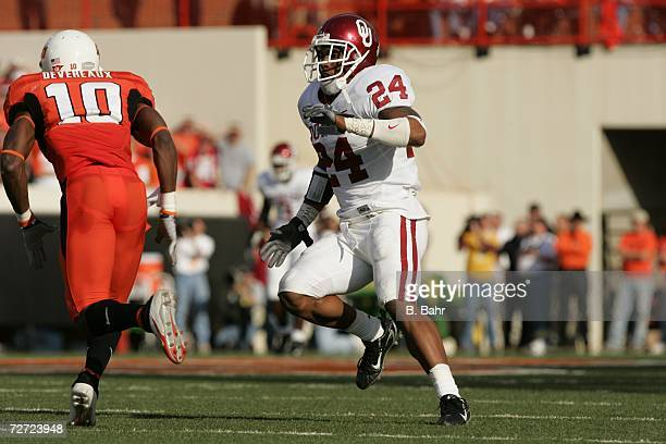 Defensive back Marcus Walker of the Oklahoma Sooners drops back to defend against wide receiver Tommy Devereaux of the Oklahoma State Cowboys on...