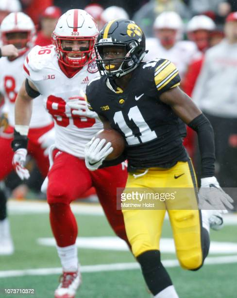 Defensive back Michael Ojemudia of the Iowa Hawkeyes runs back an interception during the second half in front of tight end Jack Stoll of the...