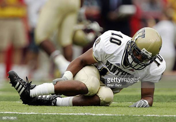 Defensive back Mike Phillips of the Pittsburgh Panthers grabs at his clearly broken leg or ankle after breaking up a pass intended for wide receiver...