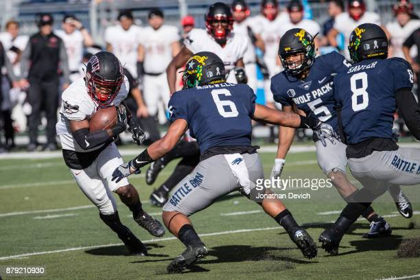 Defensive back Nephi Sewell of the Nevada Wolf Pack moves to block running back Lexington Thomas of the UNLV Rebels at Mackay Stadium on November 25...