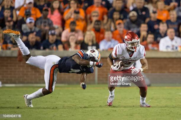 Defensive back Noah Igbinoghene of the Auburn Tigers looks to tackle running back Chase Hayden of the Arkansas Razorbacks at JordanHare Stadium on...