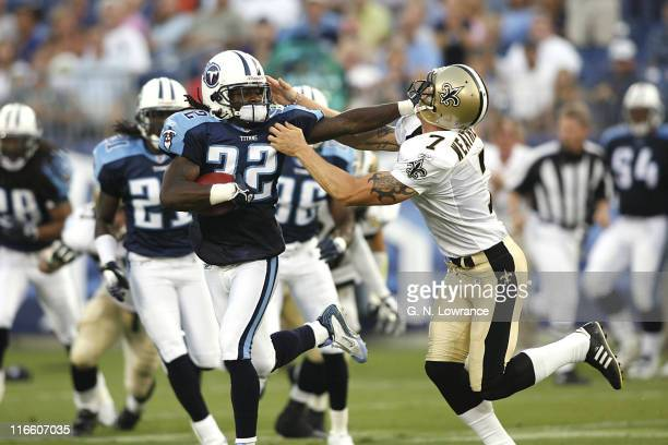 Defensive back Pacman Jones of the Titans gives Saints punter Steve Weatherford a stiff arm during action between the New Orleans Saints and the...