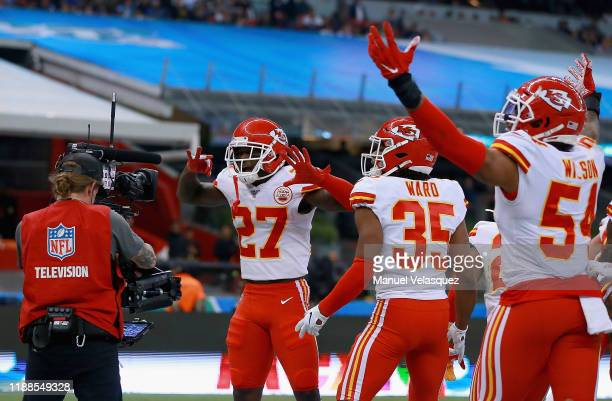 Defensive back Rashad Fenton of the Kansas City Chiefs and teammates celebrate an interception in front of a television cameraman in the fourth...