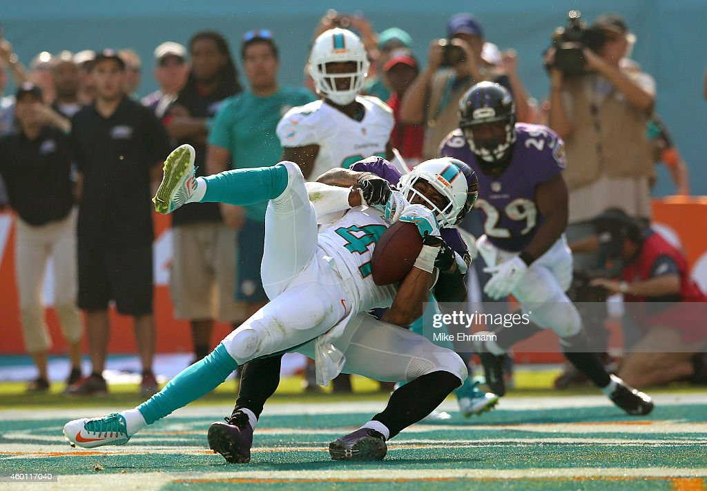 Defensive back R.J. Stanford #41 of the Miami Dolphins intercepts a second-quarter pass in the endzone as wide receiver Steve Smith #89 of the Baltimore Ravens defends during a game at Sun Life Stadium on December 7, 2014 in Miami Gardens, Florida.