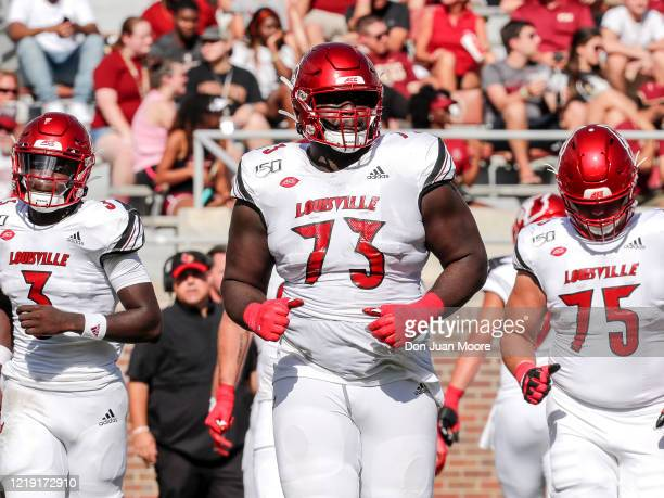 Defensive Back Russ Yeast Tackle Mekhi Becton and Guard Robbie Bell of the Louisville Cardinals take to the field during the game against the Florida...