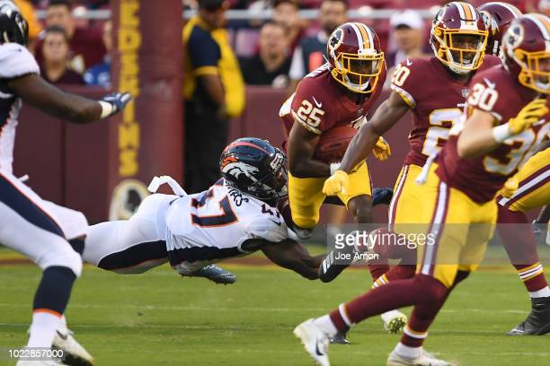 Defensive back Shamarko Thomas of the Denver Broncos trips up defensive back Greg Stroman of the Washington Redskins in the first quarter of their...