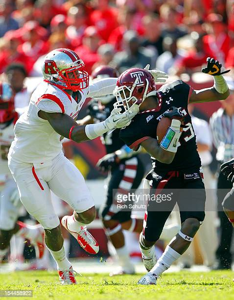 Defensive back Tavon Young of the Temple Owls is tackled by running back Desmon Peoples of the Rutgers Scarlet Knights after intercepting a pass...
