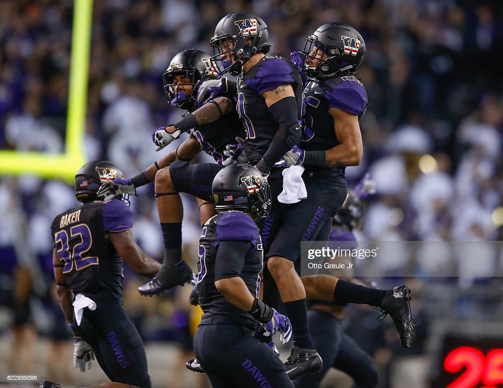 Defensive back Taylor Rapp #21 (M) of the Washington Huskies celebrates with teammates after making an interception against the USC Trojans on November 12, 2016 at Husky Stadium in Seattle, Washington. The Trojans defeated the Huskies 24-13.