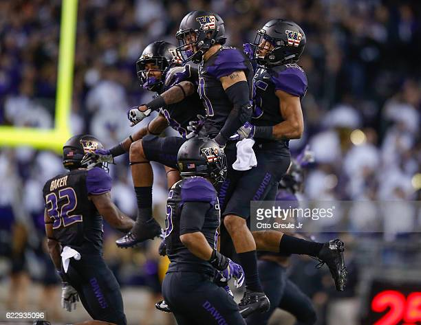 Defensive back Taylor Rapp of the Washington Huskies celebrates with teammates after making an interception against the USC Trojans on November 12...