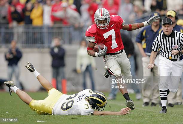 Defensive back Ted Ginn Jr #7 of the Ohio State Buckeyes runs around punter Adam Finley of the Michigan Wolverines for an 82yard touchdown return...