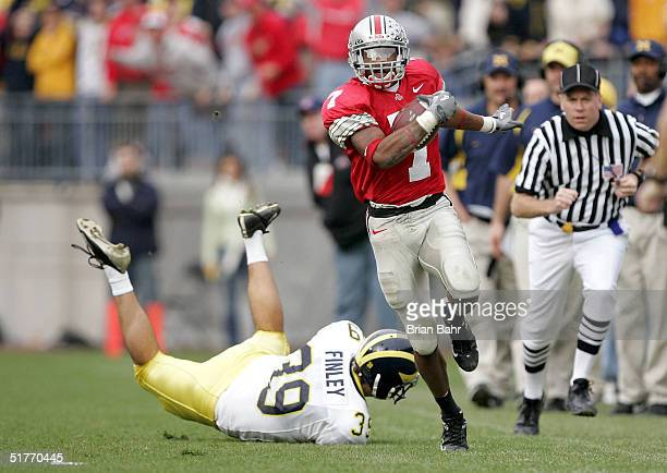 Defensive back Ted Ginn Jr #7 of the Ohio State Buckeyes runs past punter Adam Finley of the Michigan Wolverines for an 82yard touchdown return...