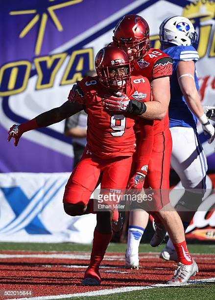 Defensive back Tevin Carter of the Utah Utes celebrates with defensive end Hunter Dimick after Carter made his second interception of the game...